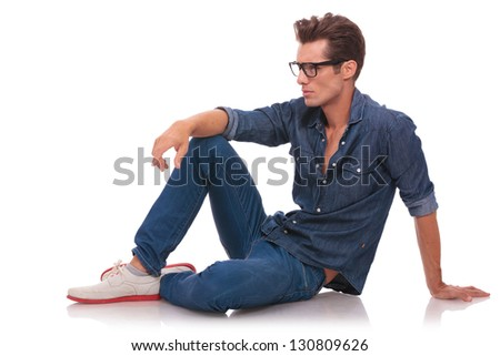 casual young man on the floor looking away from the camera with a serious look on his face. isolated on white - stock photo