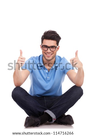 casual young man sitting cross legged showing thumbs up with both hands and smiling to the camera - stock photo