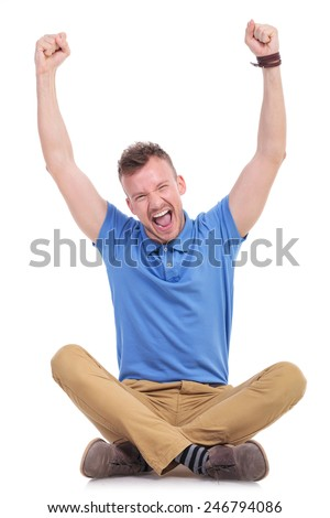 casual young man sitting on the floor with his legs crossed and cheering with both hands raised in the air. isolated on white - stock photo