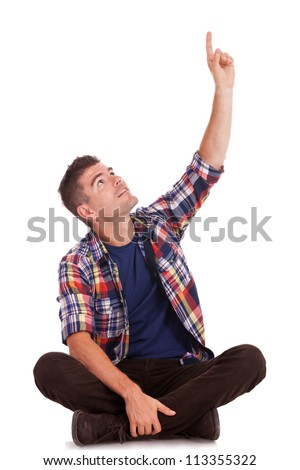 casual young man sitting on the floor with his legs crossed like lotus position, pointing and looking up. isolated on white background - stock photo