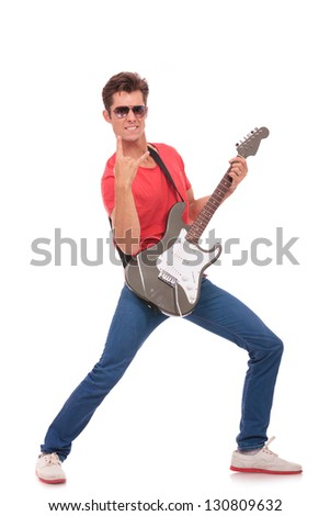 casual young man standing in a rock pose with his electric guitar in one hand and showing the rock and roll gesture with the other while biting his lip. isolated on a white background