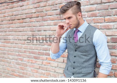 Casual young man standing next to a brick wall with a cigarette in his