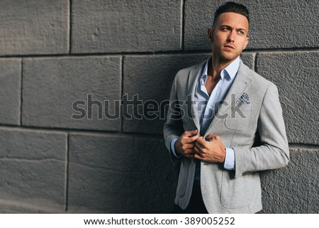 Casual young man standing with his back against a brick wall - stock photo