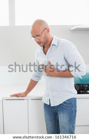 Casual young man suffering from chest pain standing at home - stock photo