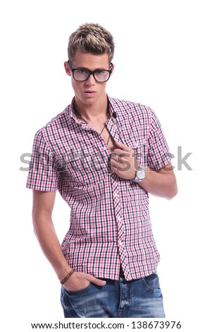 casual young man unbuttoning his shirt while looking at the camera with a hand in pocket. on background