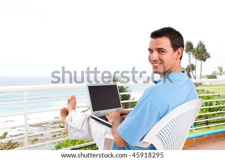 casual young man using laptop on balcony with sea view behind