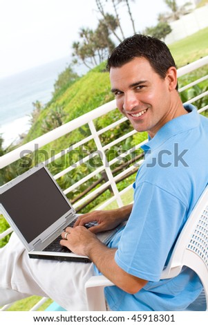 casual young man using laptop on balcony with sea view behind - stock photo