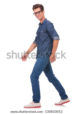 casual young man walking away from the camera while looking at it. isolated on a white background - stock photo