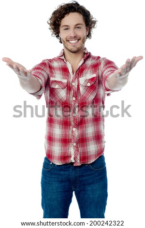 Casual young man welcoming you with his arms opened - stock photo
