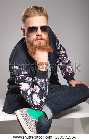 casual young man with a long red beard posing in a contemplative manner, sitting with one leg over the other and his hand at his chin, while looking into the camera. in a gray background studio - stock photo