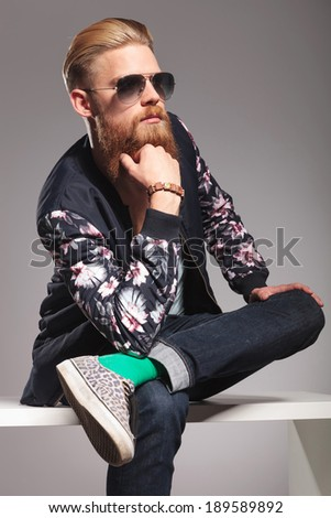 casual young man with a long red beard posing in a contemplative manner, with one leg over the other and his hand at his chin, while looking away from the camera. in a gray background studio - stock photo