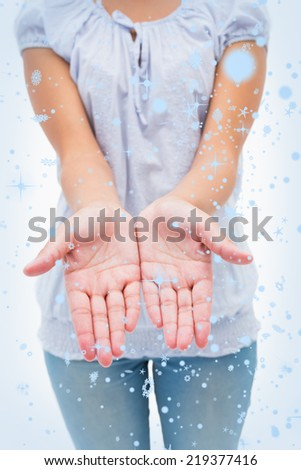 Casual young woman holding hands out against snow falling