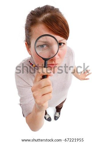 Casual young woman looking through magnifier lens as detective, analyzing or finding something - stock photo