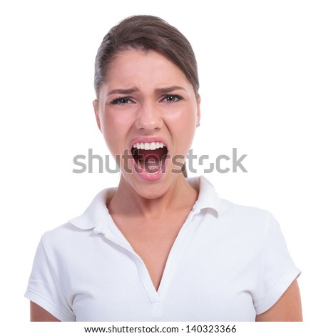 casual young woman shouting at the camera with a big opened mouth. isolated on white background