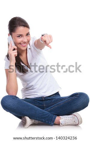 casual young woman sitting with legs crossed and pointing at the camera while speaking on the phone. isolated on white background - stock photo