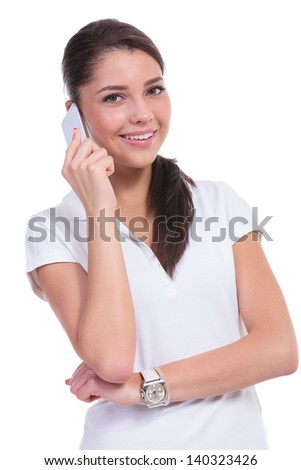 casual young woman talking with someone on the phone while smiling to the camera. isolated on white background - stock photo