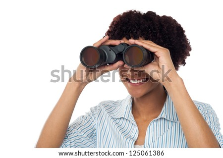 Casual young woman watching closely through binoculars.