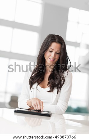 Casual Young Woman with Digital Tablet in Showcase Home