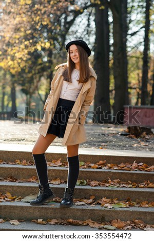 Casually dressed. Beautiful teen girl posing on the steps in an autumn park smiling to the camera soft focus