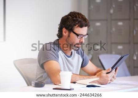Casually Dressed Man Using Digital Tablet In Design Studio - stock photo