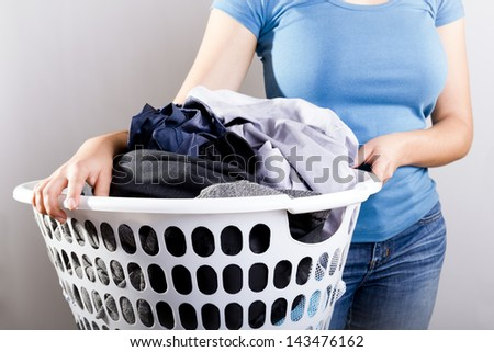 Casually dressed woman in blue shirt holding a basket full of dirty laundry needing washing - stock photo