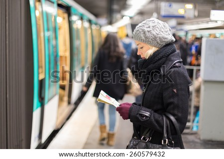 Casually dressed woman wearing winter coat, waiting on a platform for a train to arrive, orientating herself with public transport map. Urban transport. - stock photo