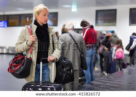 Casually dressed young female traveller waiting in airport arrival terminal hall,  collecting her laggage . Blured background. Can also be used as railway, metro, bus station. - stock photo
