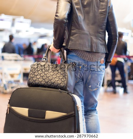 Casually dressed young stylish female traveller walking the airport terminal hall   draging suitcase and a handbag behind her. Blured background. Can also be used as railway, metro, bus station. - stock photo