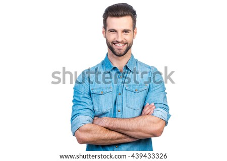 Casually handsome. Confident young handsome man in jeans shirt keeping arms crossed and smiling while standing against white background  - stock photo
