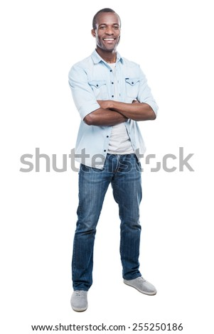 Casually handsome. Full length of handsome young black man keeping arms crossed and smiling at camera while standing against white background  - stock photo