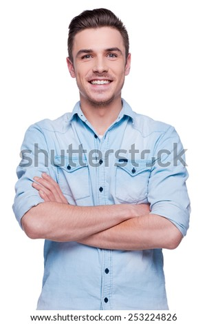 Casually handsome. Handsome young man in shirt looking at camera and keeping arms crossed while standing against white background  - stock photo