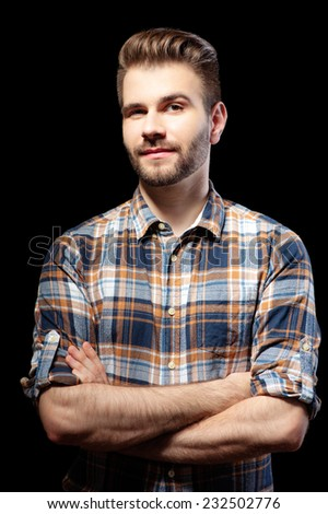Casually handsome. Portrait of handsome young man in casual shirt keeping arms crossed and looking at camera while standing isolated on black. - stock photo