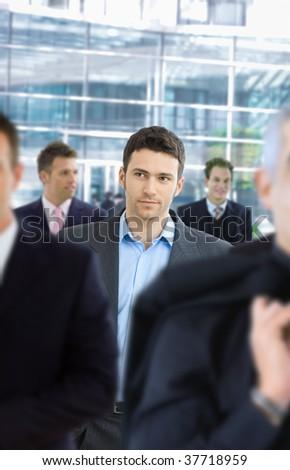 Casul businessman walking in crowd in office lounge. - stock photo