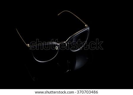 Cat eyes shaped retro glasses on black background - stock photo