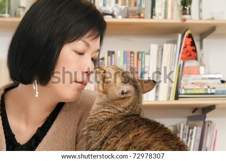 Cat kiss her master, woman with pet in home. - stock photo