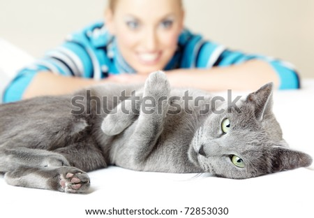 Cat pampering indoors and defocused smiling woman