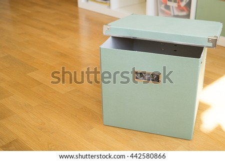 Cat peeks through a hole in box whilst playing hide and seek - stock photo