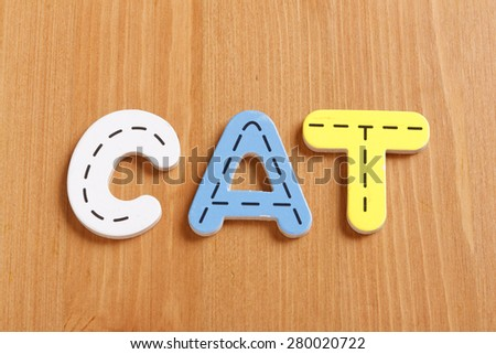 CAT, spell by woody puzzle letters with woody background - stock photo