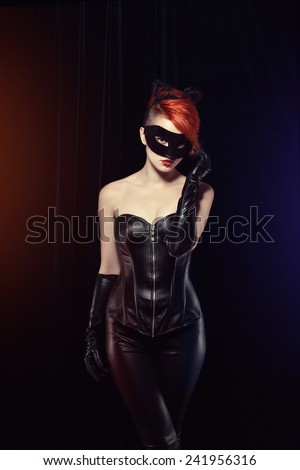 Cat woman with red hair in a leather suit with ears of a cat with a mask and makeup leather gloves - stock photo