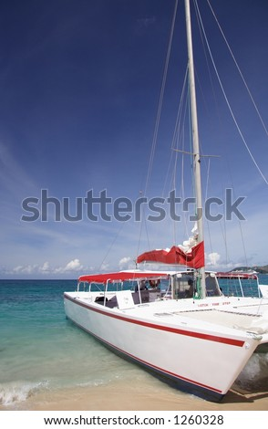 Catamaran on a beautiful caribbean beach - stock photo