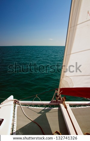 Catamaran sailboat with white and red set sail, sailing on a beautiful cloudless blue sky day and calm blue ocean waters - stock photo