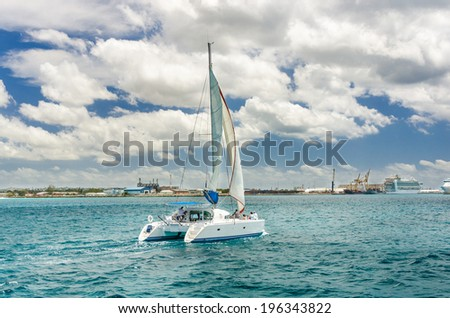Catamaran Sailing off the Coast of Barbados on a Cloudy Day - stock photo