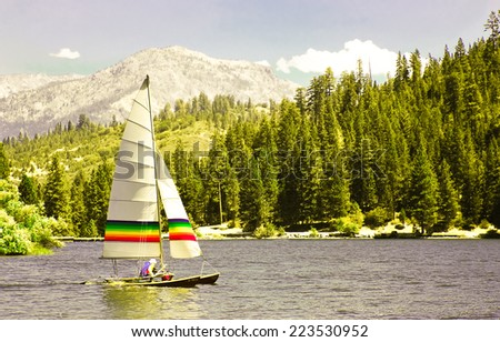 Catamaran sailing smoothly on the surface of a mountain lake. - stock photo