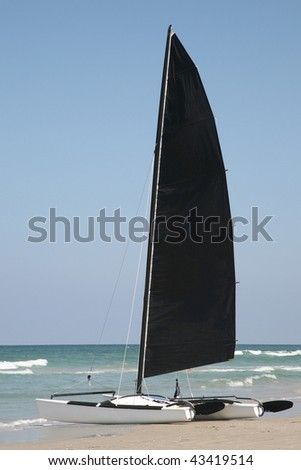 Catamaran with black sail at the beach - stock photo