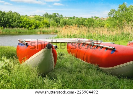 Catamarans for rafting on the river bank - stock photo
