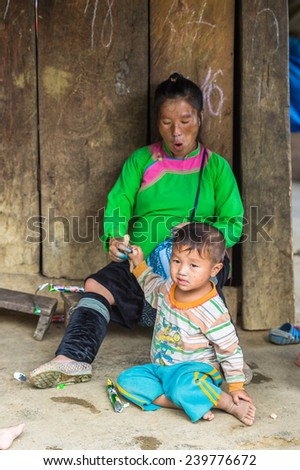 CATCAT, VIETMAN - SEP 20, 2014: Unidentified Hmong little boy plays on the ground and his mother watches  Catcat village, Vietnam. Hmong is a minority ethnic group of Vietnam