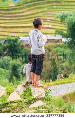 CATCAT, VIETMAN - SEP 20, 2014: Unidentified Hmong little boys watching beautiful nature in Catcat village, Vietnam. Hmong is a minority ethnic group of Vietnam