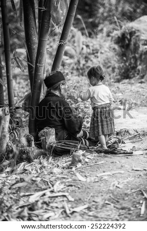 CATCAT, VIETMAN - SEP 20, 2014: Unidentified Hmong woman and her little grand daughter in CatCat village, Vietnam. Hmong is a minority ethnic group of Vietnam