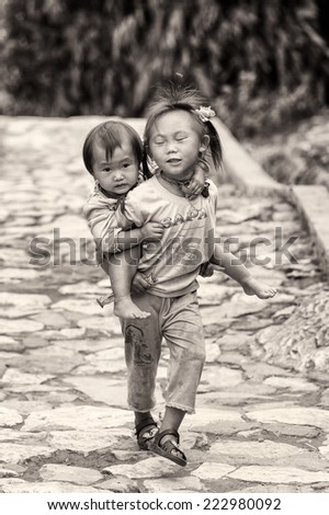 CATCAT VILLAGE, VIETMAN - SEP 12, 2014: Unidentified Vietnamese beautiful girl carries her sister in the Catcat village, Vietnam. 86% of Vietnamese people belong to the Viet ethnic group