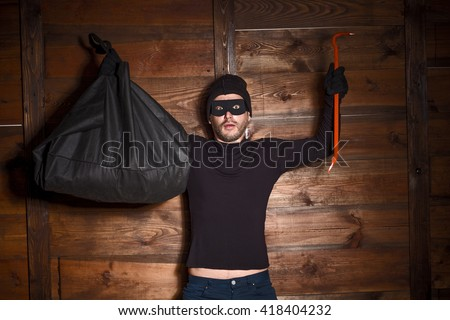 Catch burglar concept, thief with balaclava caught in front of wooden wall of someone's house. Man standing with his hands up.